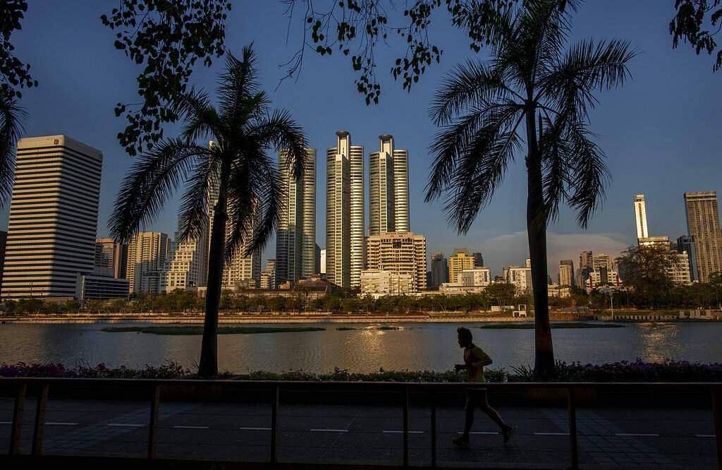 A man jogs in a park, as the streets are empty in Bangkok, and a month-long state of emergency has been enforced in Thailand to control the coronavirus. (AP Photo/Gemunu Amarasinghe)