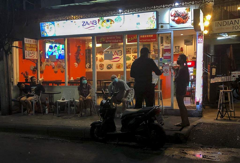 A policeman tells a restaurant owner to stop people from socialising, as a month-long state of emergency has been enforced in Thailand to control the coronavirus. (AP Photo/Gemunu Amarasinghe)