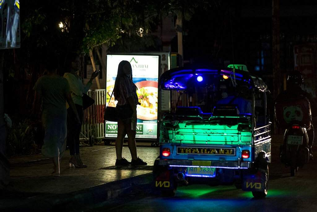 Sex workers stand in a largely shut-down red light area in Bangkok, as a month-long state of emergency has been enforced in Thailand to control the coronavirus. (AP Photo/Gemunu Amarasinghe)