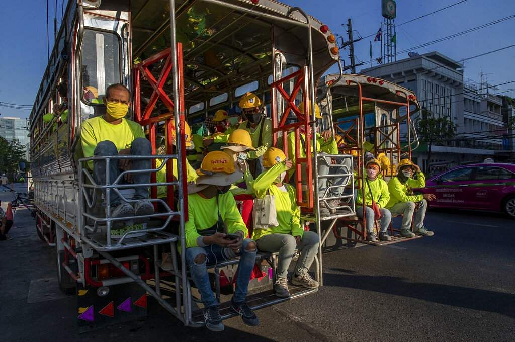Migrant construction workers in a truck after a day's work are reflected in a mirror in Bangkok, as an emergency has been enforced in Thailand. (AP Photo/Gemunu Amarasinghe)