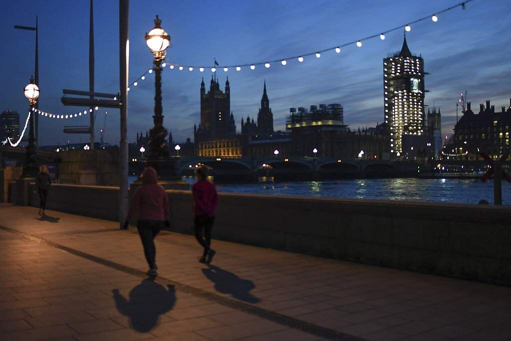London, United Kingdom: A few people run along the almost deserted South Bank of the River Thames, with the parliament in the background. (AP Photo/Alberto Pezzali)