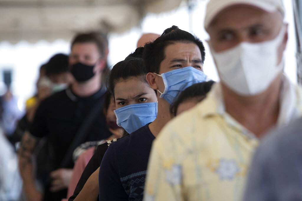 Tourists gather at the Immigration Bureau to extend their visa in Bangkok. Tourists across Asia are finding their dream vacations have turned into travel nightmares. (AP Photo/Sakchai Lalit)