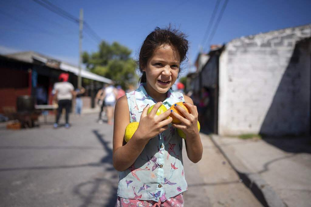 Buenos Aires, Argentina: Laila, 9, walks home with an armful of oranges she received at a soup kitchen, on the outskirts of Buenos Aires. (AP Photo/Victor R Caivano)