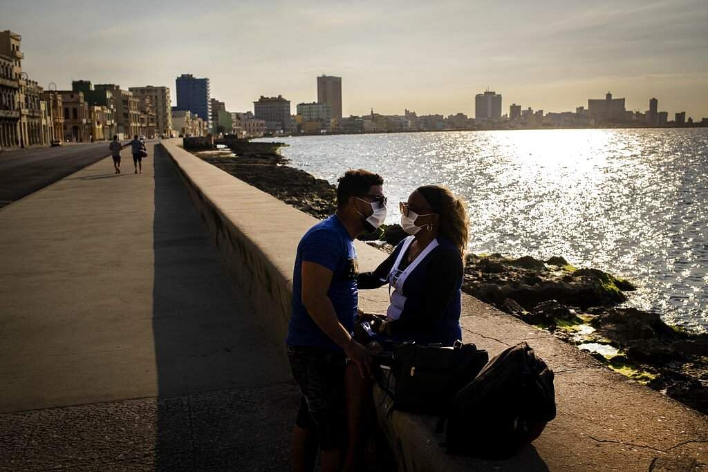 Havana, Cuba: A couple wearing face masks spend the afternoon at the malecon in Havana. (AP Photo/Ramon Espinosa)