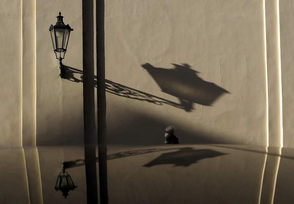 Prague, Czech Republic: A woman wearing a face mask walks alone in downtown Prague. (AP Photo/Petr David Josek)