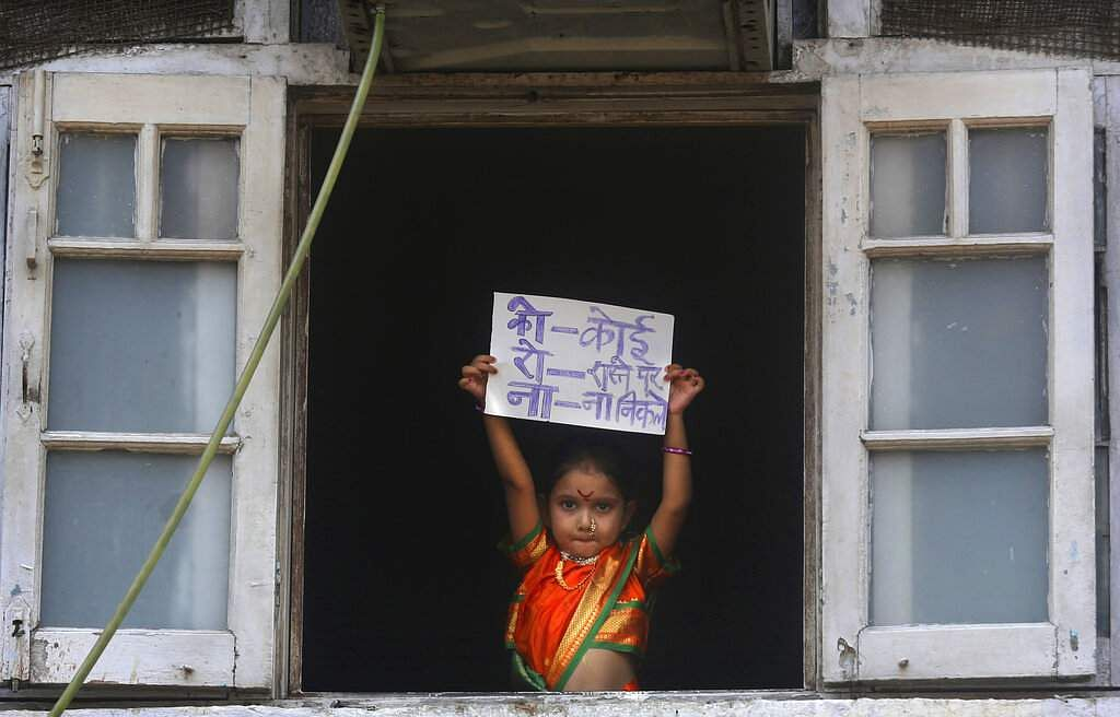 Mumbai, India: On Gudi Padwa, the Marathi New Year, a girl holds a placard with an acronym for the coronavirus in Hindi that says, 'Nobody should come out on the roads'. (AP Photo/Rafiq Maqbool)