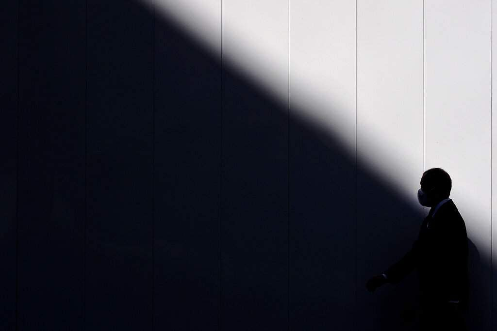 Tokyo, Japan: A man wearing a mask is silhouetted against a wall as he walks into the shade of a building in Tokyo. (AP Photo/Jae C Hong)