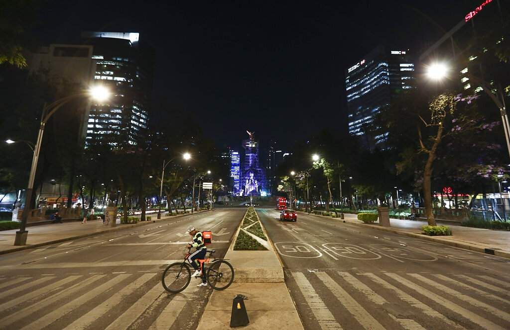 Mexico City, Mexico: A food delivery worker crosses Reforma Avenue, normally severely congested with traffic, in Mexico City. (AP Photo/Eduardo Verdugo)