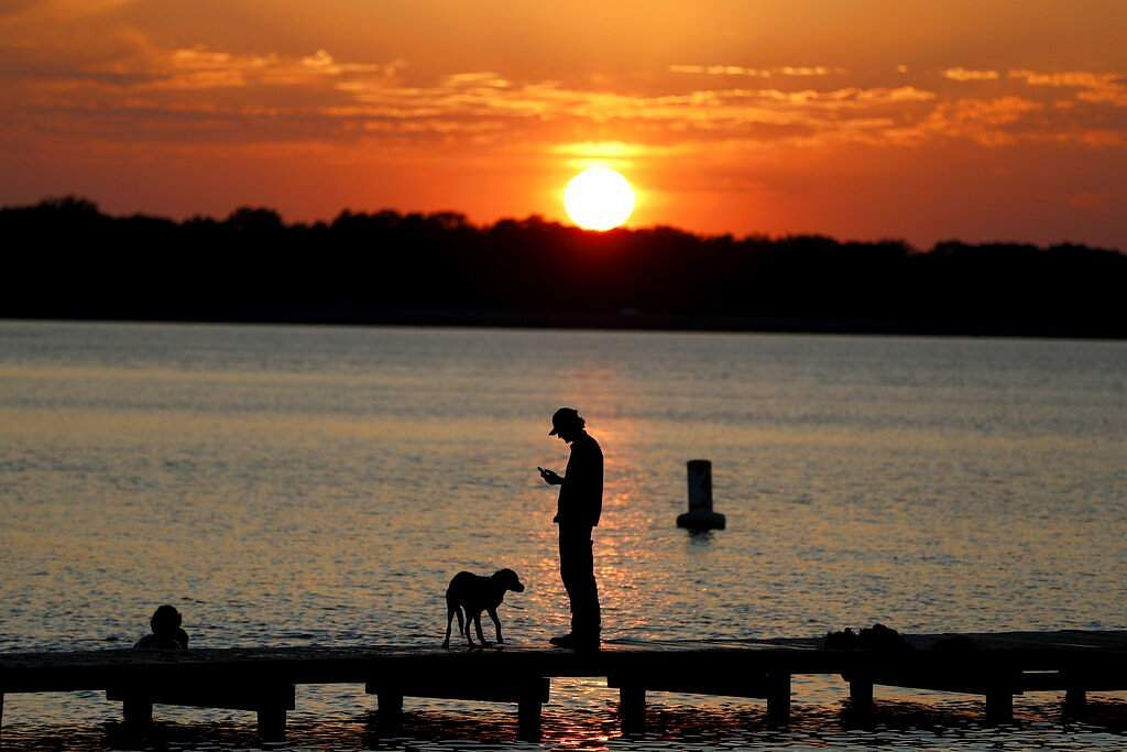 Brandon, Mississippi: Brandon Derbyshrie, 20, checks his cell phone while standing by a friend's dog named Riley at Lakeshore Parl, as the sun begins to set over the horizon. (AP Photo/Julio Cortez)