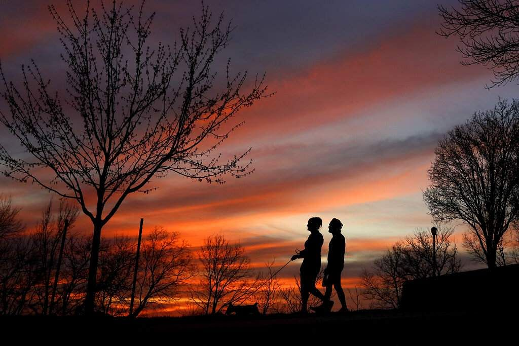 Kansas City, Missouri: A couple walk a dog at sunset in Kansas City, which along with its neighbouring counties is under 'Stay at Home' orders. (AP Photo/Charlie Riedel)