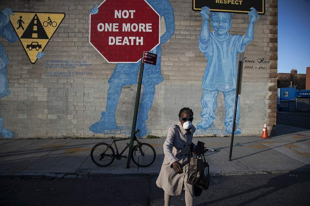 New York, USA: A woman wearing a mask crosses the street in front of a mural about traffic accidents reading, 'NOT ONE MORE DEATH' in the Brooklyn borough of New York. (AP Photo/Wong Maye-E)
