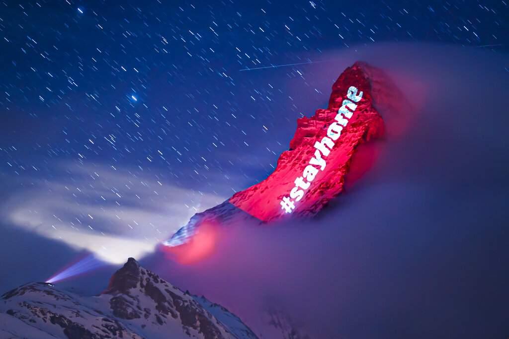 Zermatt, Switzerland: The Matterhorn mountain is illuminated by Swiss light artist Gerry Hofstetter sends out a message during the global coronavirus pandemic. (Valentin Flauraud/Keystone via AP)