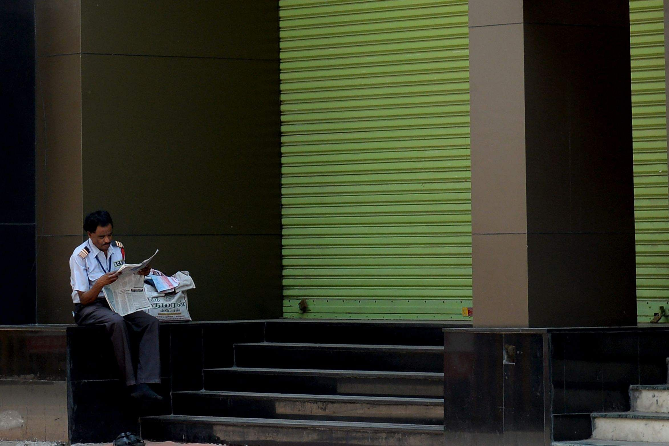Chennai, India: A security personnel reads a newspaper in front of a closed shop during the 21-day government-imposed nationwide lockdown to contain the coronavirus pandemic. (AFP/Arun SANKAR)