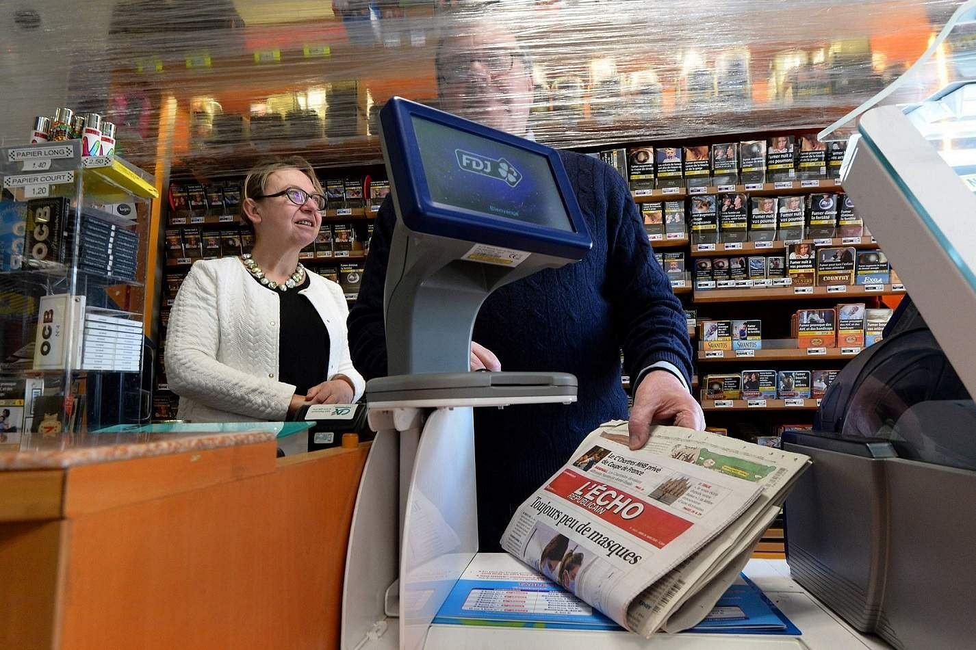 Illiers-Combray, Eure-et-Loir, France: Newspaper retailers protect themselves behind a plastic film attached over their counter in Illiers-Combray, western France. (AFP/JEAN-FRANCOIS MONIER)