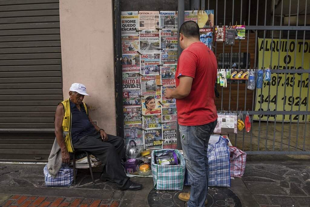 Lima, Peru: A man reads newspaper front pages as the vendor takes a nap in downtown Lima. (AP Photo/Rodrigo Abd)