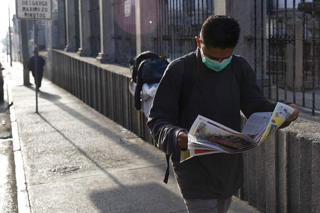 Guatemala City, Guatemala: A man wearing a protective mask reads a newspaper in Guatemala City. (AP Photo/Moises Castillo)