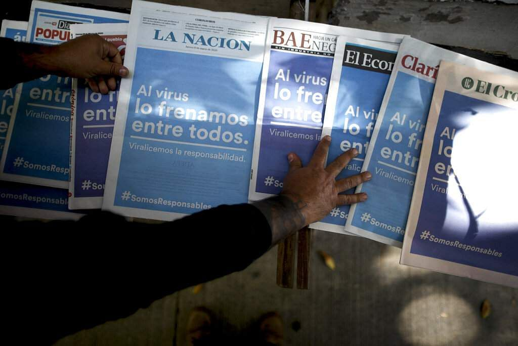 Buenos Aires, Argentina: A vendor shows the front pages of several newspapers carrying the same Spanish headline, 'Between all of us, we put the breaks on the virus'. (AP Photo/Natacha Pisarenko)