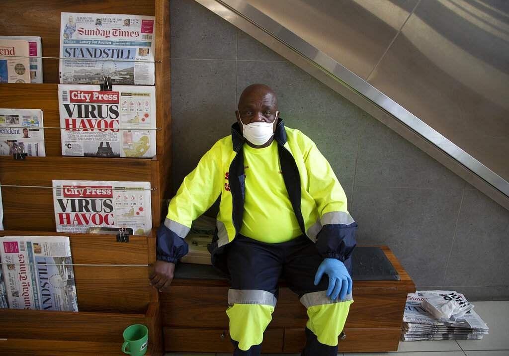 Johannesburg, South Africa: A masked newspaper seller waits to make a sale in the virtually empty Rosebank Mall in Johannesburg. (AP Photo/Denis Farrell)