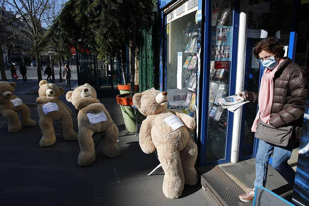 Paris, France: A woman wearing a protective mask walks out with her newspaper out of a shop with bears installed in line in Paris. (AP Photo/Francois Mori)