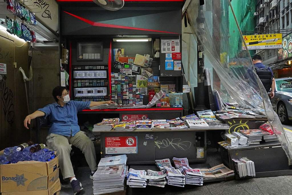 Hong Kong: A vendor wearing a face mask takes a break at a newspaper booth in Hong Kong. (AP Photo/Vincent Yu)