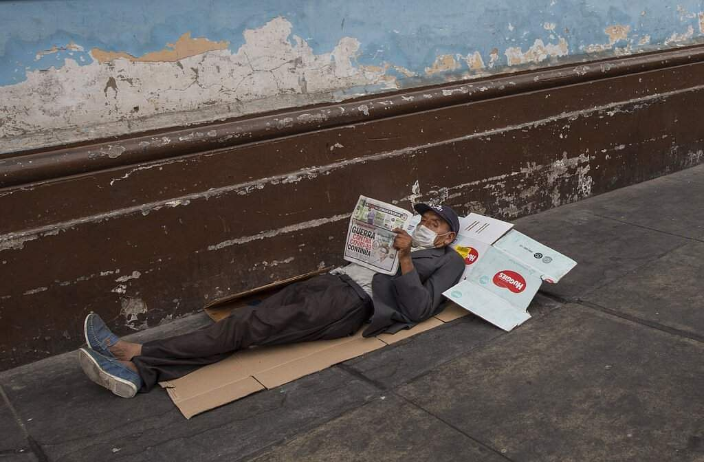 Lima, Peru: A homeless man reads a newspaper in which the front page reads in Spanish, 'War against COVID-19 Continues', on a sidewalk in downtown Lima. (AP Photo/Rodrigo Abd)