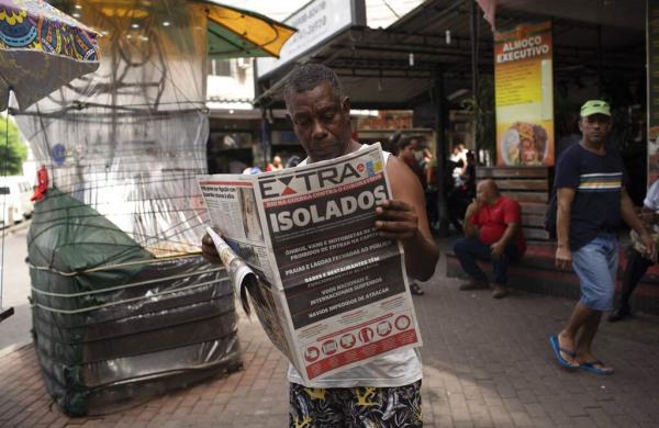 Rio de Janeiro, Brazil: A man reads a newspaper with the Portuguese headline, 'Isolated. Rio in war against coronavirus' in the Rocinha slum of Rio de Janeiro. (AP Photo/Silvia Izquierdo)