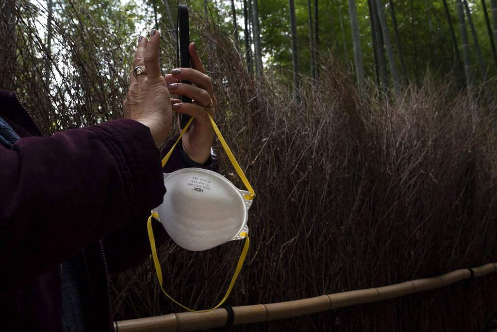 A tourist holds a mask while taking pictures of the Arashiyama Bamboo Forest in Kyoto, Japan. (AP Photo/Jae C Hong)