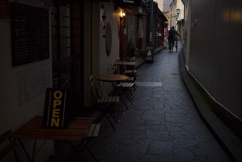 A man walks with his bike through a narrow alley lined with restaurants in Nara, Japan. (AP Photo/Jae C Hong)