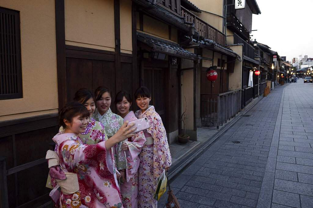 A group of Japanese women wearing kimonos take a selfie in the Gion district of Kyoto, Japan. Tourism has taken a beating after Beijing banned group tours in late January. (AP Photo/Jae C Hong)