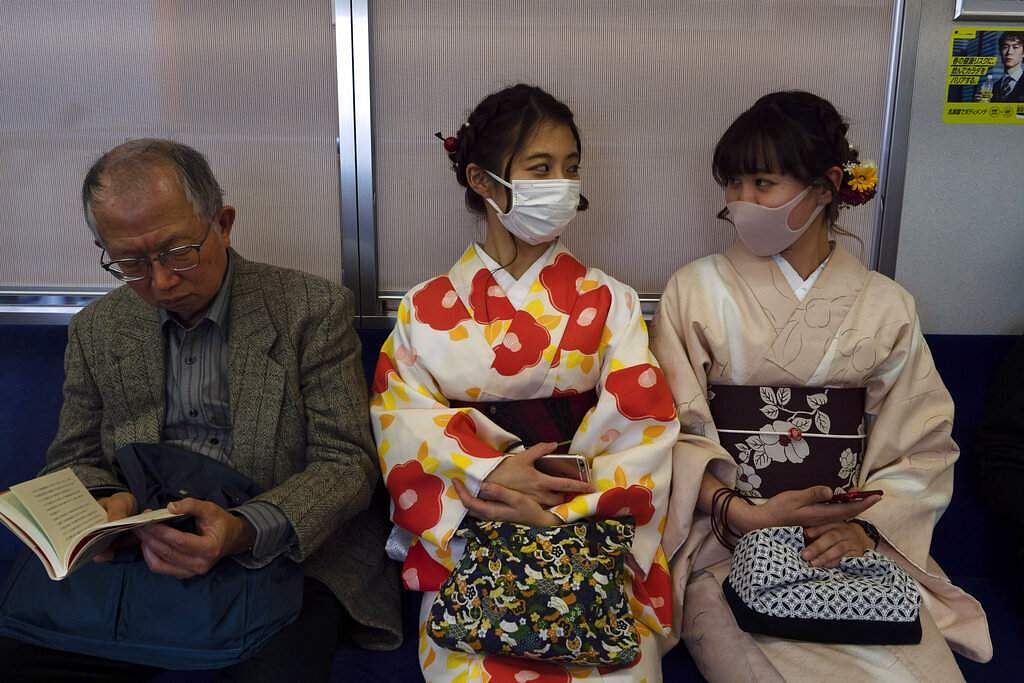 Two women wearing kimonos chat in a train in Kyoto, Japan. The Japanese tourism industry has taken a beating after Beijing banned group tours in late January. (AP Photo/Jae C Hong)