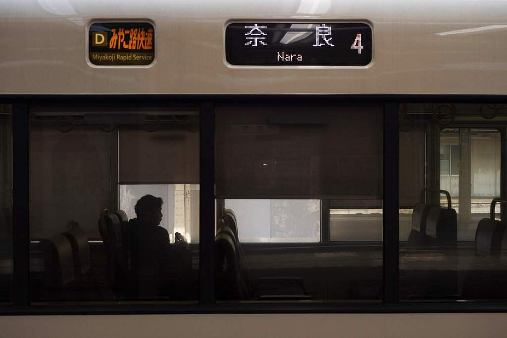 A man is silhouetted while sitting in a train bound for Nara at Kyoto Station in Kyoto, Japan. (AP Photo/Jae C Hong)