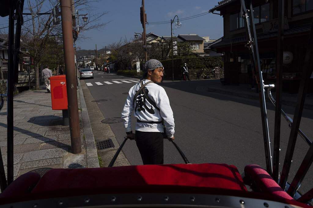 A rickshaw puller crosses the street in the Arashiyama district of Kyoto, Japan. (AP Photo/Jae C Hong)