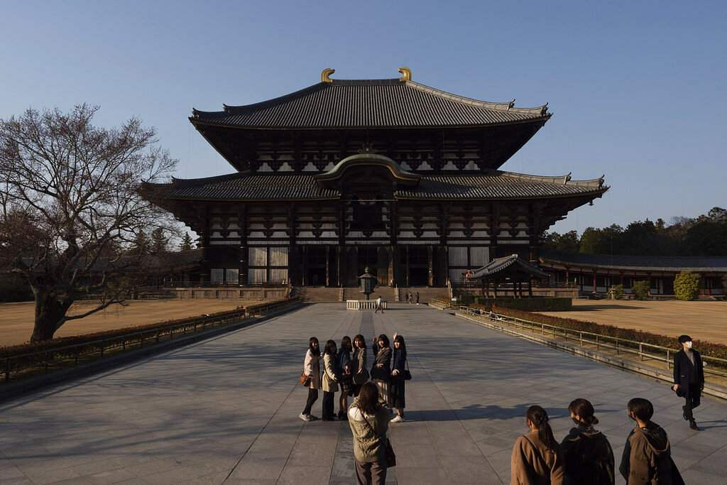 Tourists pause for photos in front of Todaiji temple's main hall in Nara, Japan. Nara was among the first Japanese town hit by the COVID-19 in late January. (AP Photo/Jae C Hong)