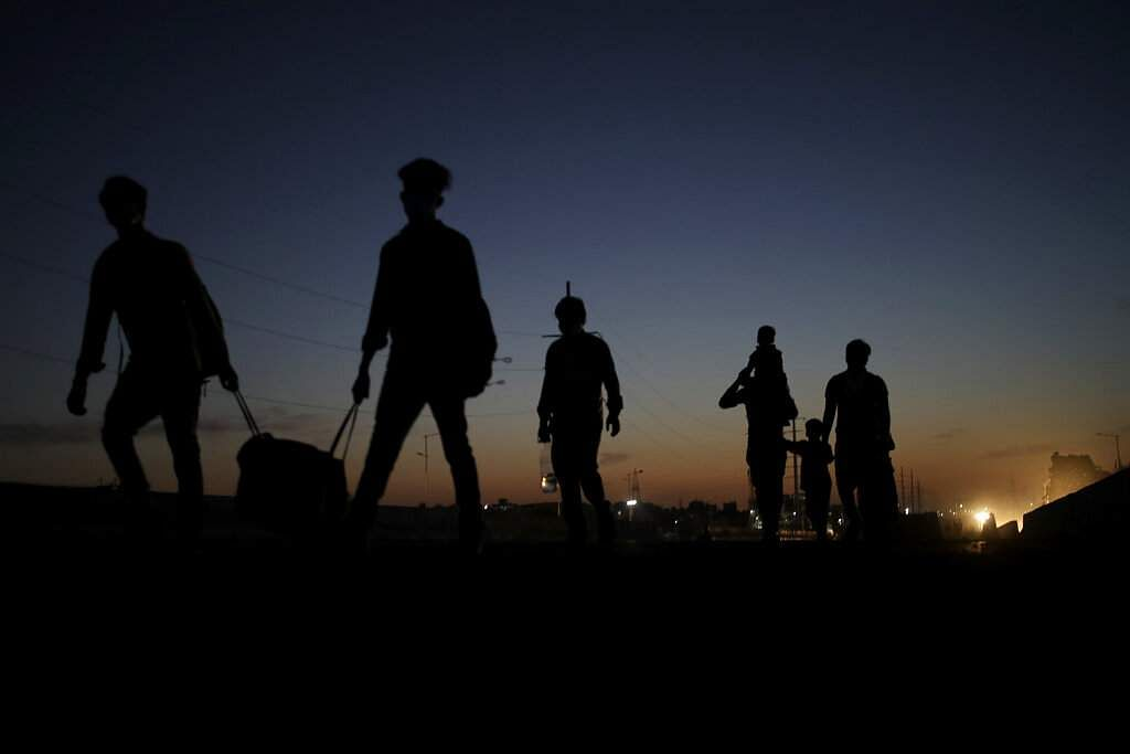 New Delhi: A migrant labourer's family is silhouetted as they proceed towards their village on foot. India is witnessing an exodus unlike anything since the 1947 Partition. (AP Photo/Altaf Qadri)