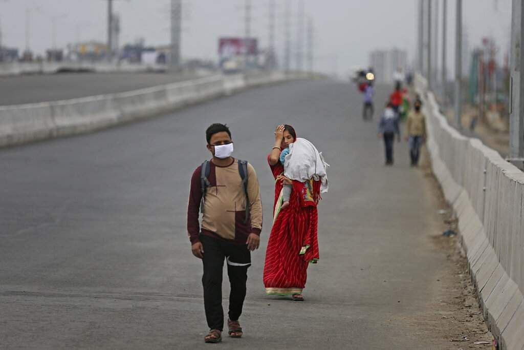Ghaziabad: A couple carrying an infant walk along an expressway hoping to reach their home, hundreds of miles away, as the city comes under lockdown, on the outskirts of Delhi. (AP Photo/Altaf Qadri)