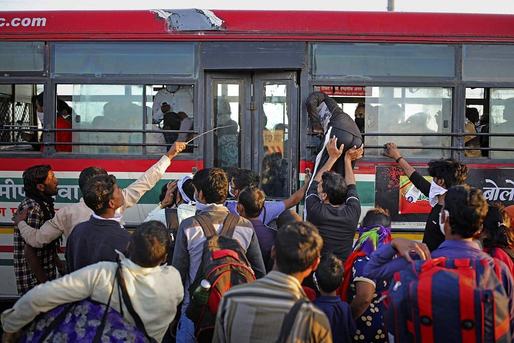 New Delhi: A migrant worker tries to make his way through a window of a government bus, as they leave for their respective villages following the nationwide lockdown. (AP Photo/Altaf Qadri)