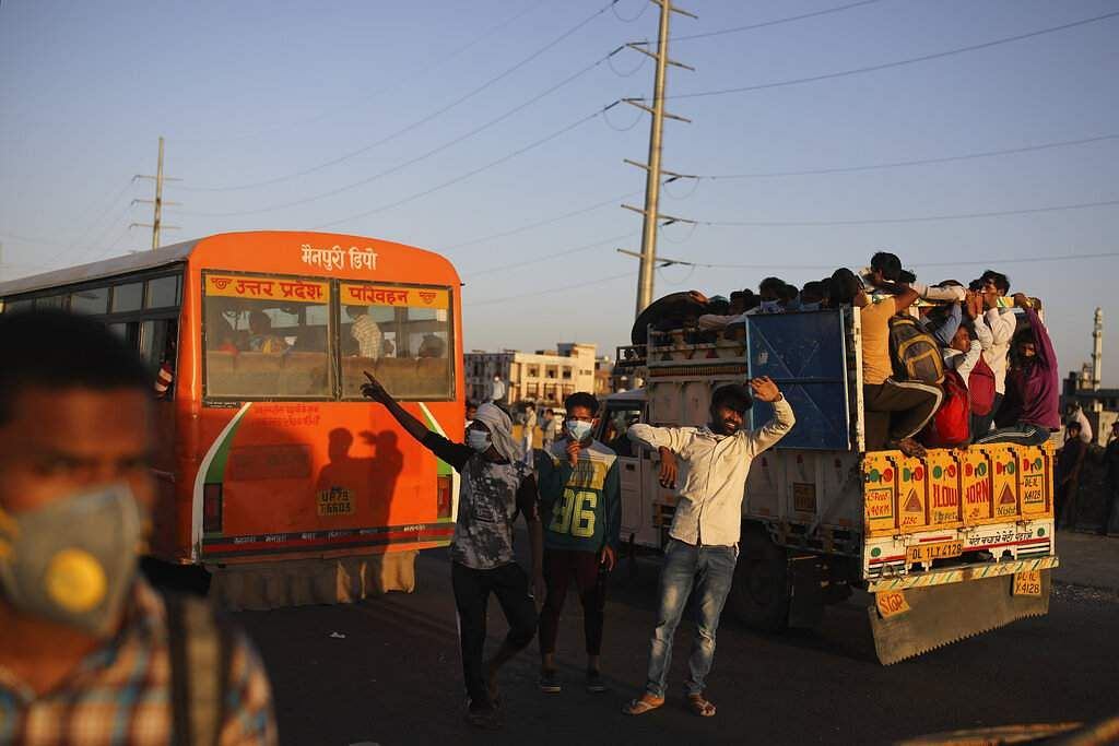 New Delhi: Indian men try to stop vehicles for migrant workers waiting for transportation to their respective villages following the nationwide lockdown. (AP Photo/Altaf Qadri)