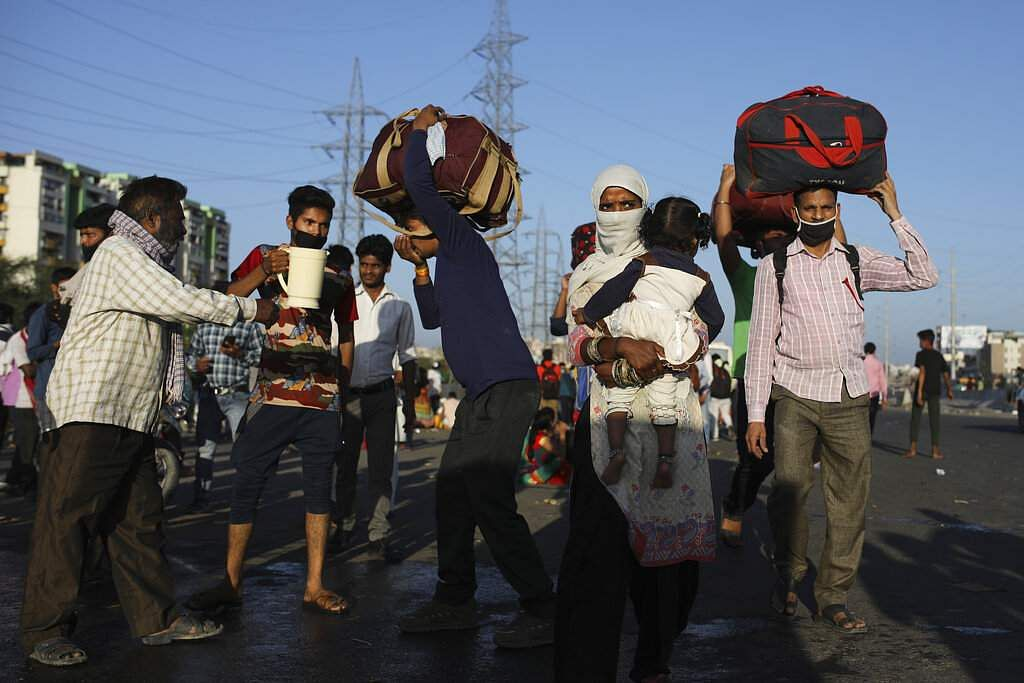 New Delhi: Locals provide drinking water to migrant labourers making their way on foot to their respective villages following the nationwide lockdown. (AP Photo/Altaf Qadri)