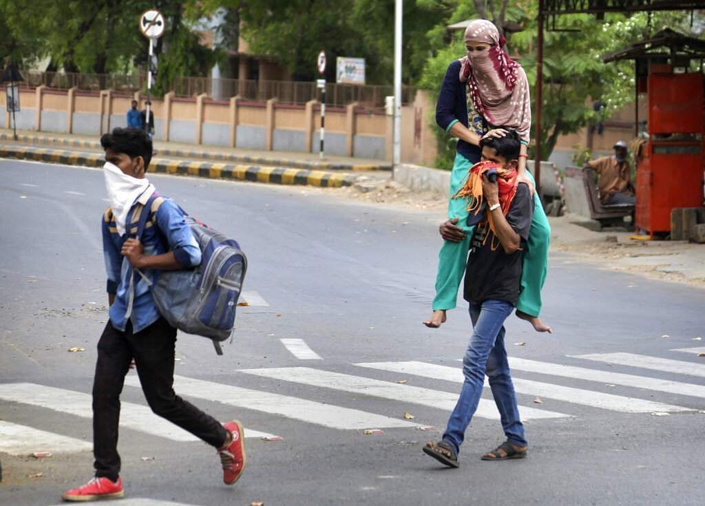 Ahmedabad: Migrant worker Ramesh Meena from Rajasthan carries her wife Ramila, who fractured her leg, as they leave for their village after the city came under lockdown. (AP Photo/Ajit Solanki)
