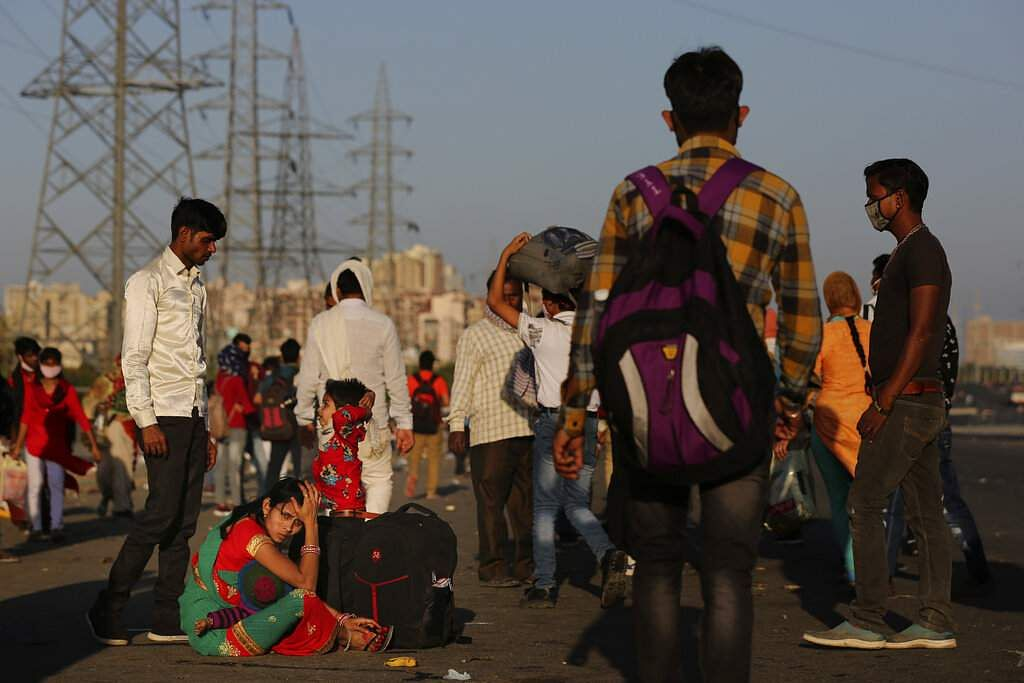 New Delhi: An Indian migrant family waits for transportation to their village following the nationwide lockdown. (AP Photo/Altaf Qadri)