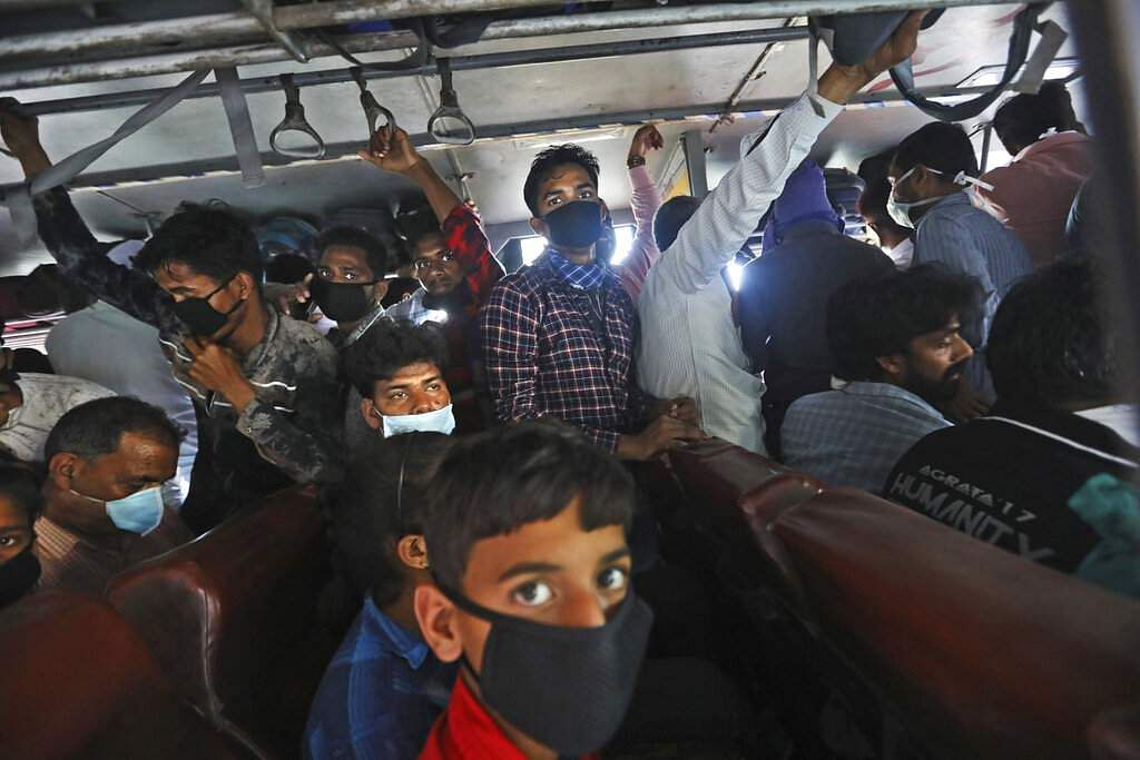 New Delhi: Migrant daily wage labourers crowd a bus as they travel to their respective hometowns following the nationwide lockdown. (AP Photo/Manish Swarup)