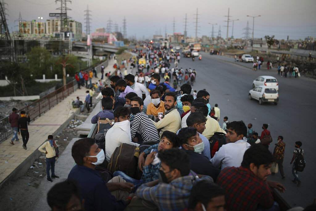 New Delhi: Indian migrant workers sit atop a bus, provided by the govt, as others walk along an expressway to their villages following the nationwide lockdown. (AP Photo/Altaf Qadri)