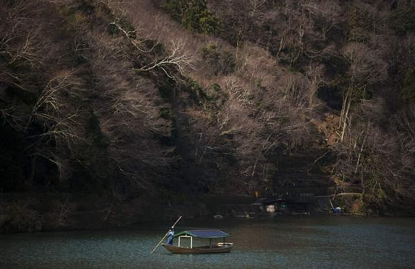 A boatman glides his boat across the river in the Arashiyama district of Kyoto, Japan. Widening travel restrictions and closures have gutted the tourism industry in Japan. (AP Photo/Jae C Hong)