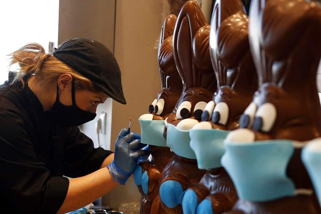 Elsewhere in Lykovrisi, northern Athens, Greece, an employee of a cake shop prepares chocolate Easter bunnies with masks. (AP Photo/Thanassis Stavrakis)