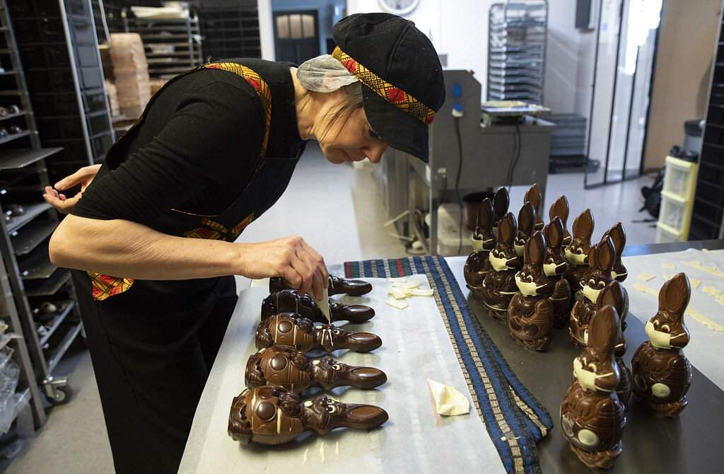 Genevieve Trepant decorates chocolates at her shop, Cocoatree, in Lonzee, Belgium. During lockdown, many shops have resorted to online sales, home delivery or pick up on site. (AP Photo/Virginia Mayo)