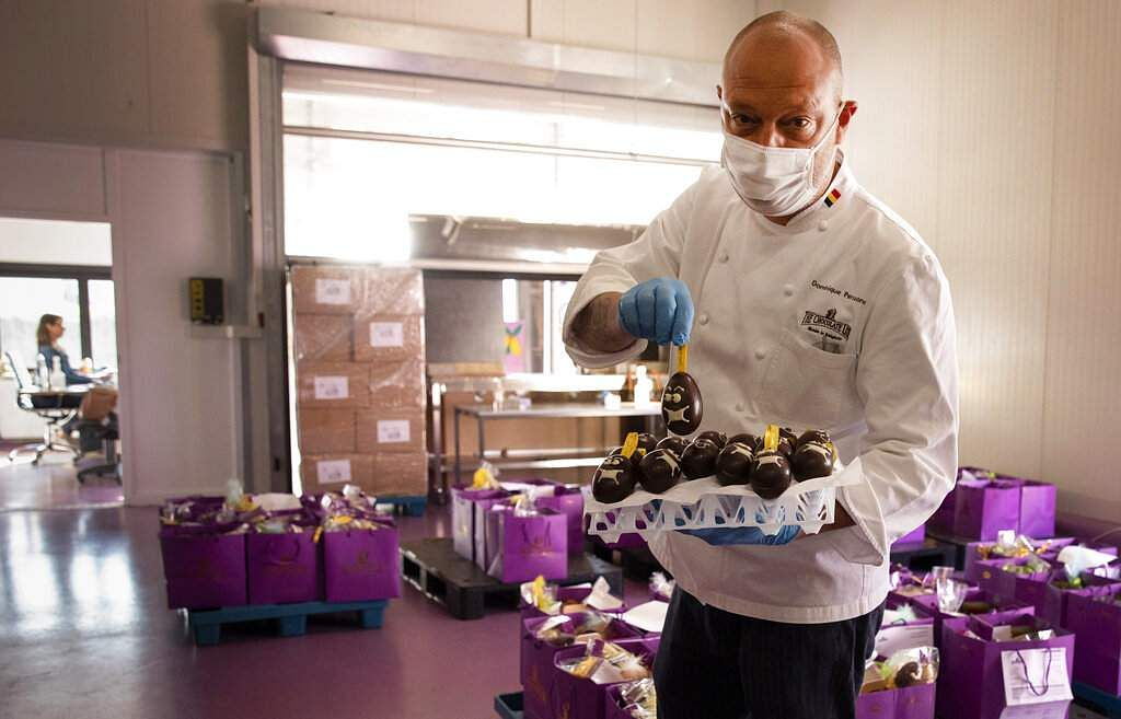One of Belgium's top chocolate producers Dominique Persoone, wearing a face mask, displays one of his chocolate Easter eggs at his Chocolate Line warehouse in Bruges, Belgium. (AP Photo/Virginia Mayo)