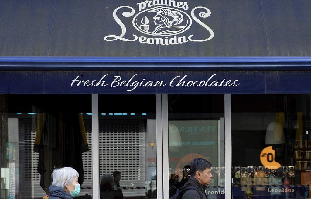 A woman in a face mask walks by the closed Leonidas chocolate shop in Antwerp, Belgium. (AP Photo/Virginia Mayo)
