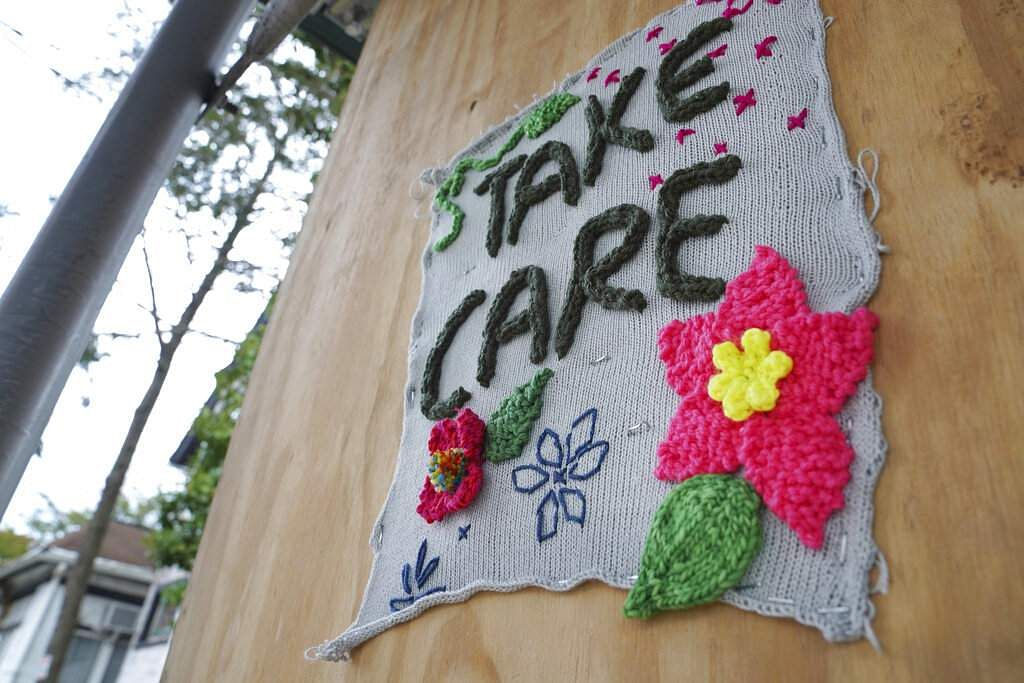 A knitted artwork that reads 'Take Care' is posted to a wooden board on a street in Brooklyn, New York. (AP Photo/Emily Leshner)