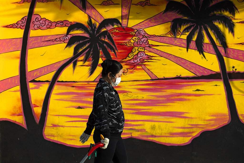 A woman walks past graffiti as she wears a protective face mask and gloves amid concerns over the country's coronavirus outbreak in Tel Aviv, Israel. (AP Photo/Oded Balilty)