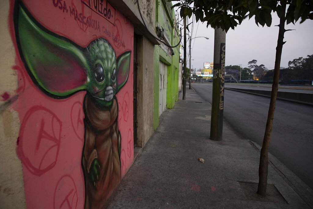 A graffiti of the Star Wars character Baby Yoda wearing wearing a face mask is painted on a wall in Guatemala City. (AP Photo/Moises Castillo)